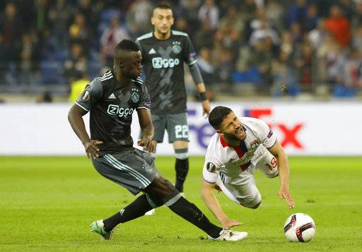 FILE - A Thursday, May 11, 2017, file photo of Ajax's Davinson Sanchez, left,  tackling Lyon's Nabil Fekir, during the second leg semi final soccer match between Olympique Lyon and Ajax in the Stade de Lyon, Decines, France. The tall Colombia center back missed Ajax's first game of the season, a 2-1 loss to Heracles Almelo in the Eredivisie, because club management didn't feel he was in the right frame of mind to play.