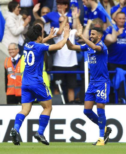 Leicester City's Shinji Okazaki, left, celebrates scoring his side's first goal with teammate Riyad Mahrez during their English Premier League soccer match against Brighton at the King Power Stadium, Leicester, England, Saturday, Aug. 19, 2017. (Nigel French/PA via AP)