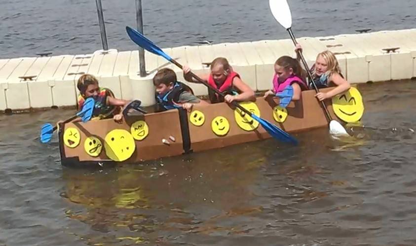 Steve Zalusky/szalusky@dailyherald.com Lorelei Denny, Cooper Schiller, Amber Martin, Grace Szczesny and Kelsey Franz prove Sunday that five can fit in a cardboard boat without it sinking, during the 20th annual Fox Lake Cardboard Cup Regatta.