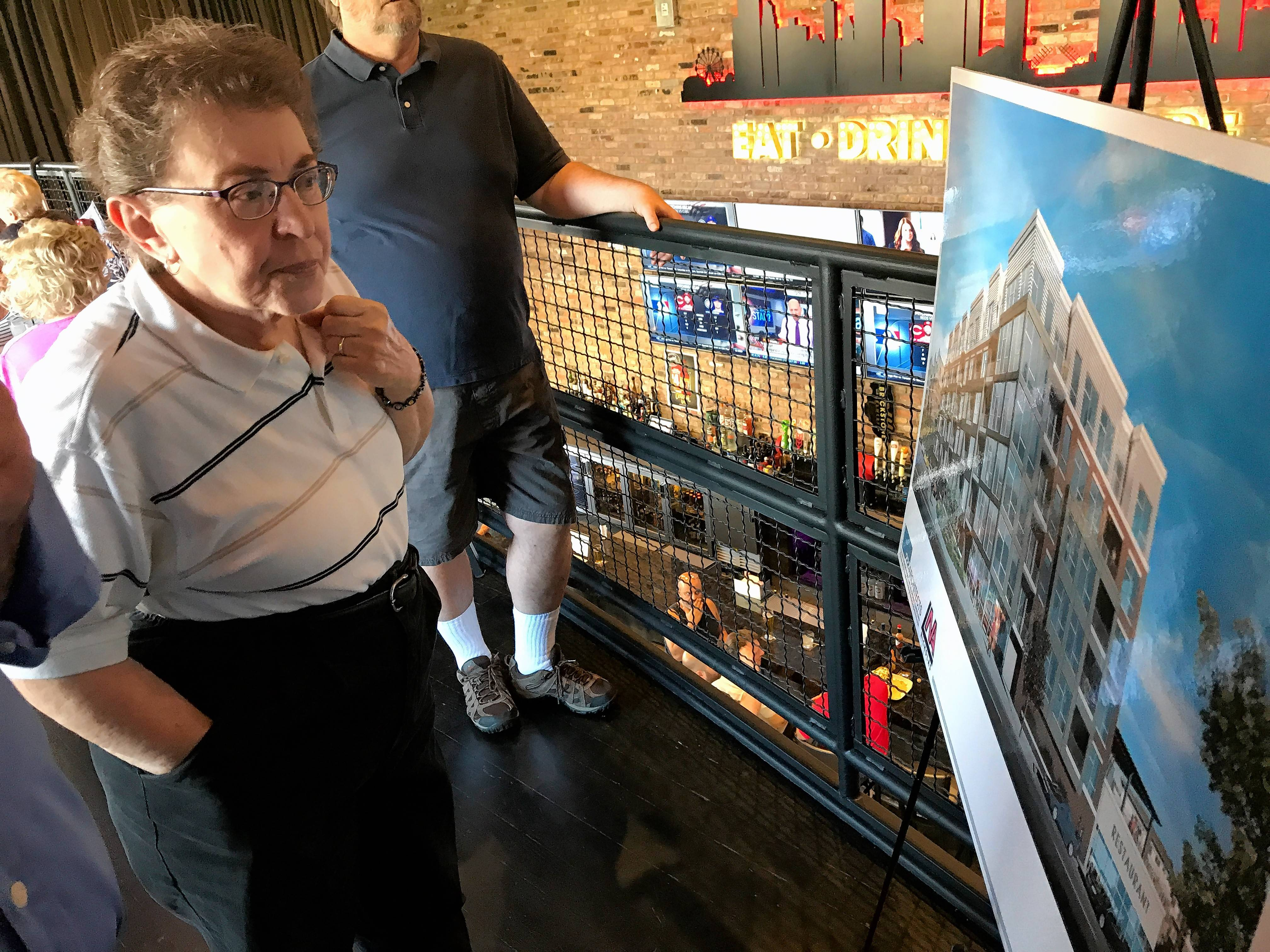 Mount Prospect resident Barb Ostrominski examines the plans for the apartment development in the village's downtown. Ostrominski and other residents say they're glad to see development on the site, but worry about traffic and parking impacts.