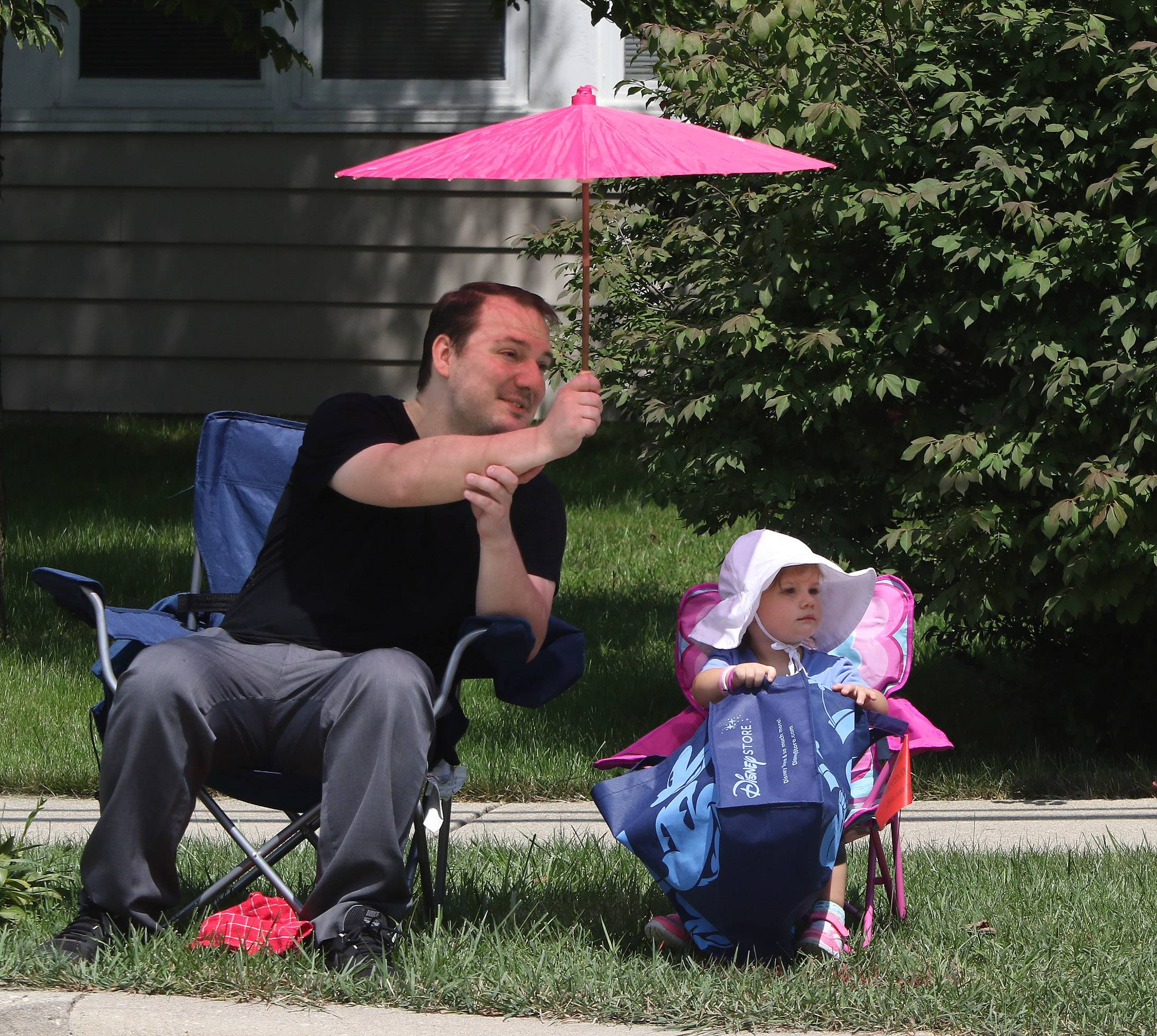 Joseph Hessel, of Gurnee holds a parasol over his daughter, Madelyn, 2, as they watch the parade travel along Old Grand Avenue during the 2017 Gurnee Days Parade on Sunday.