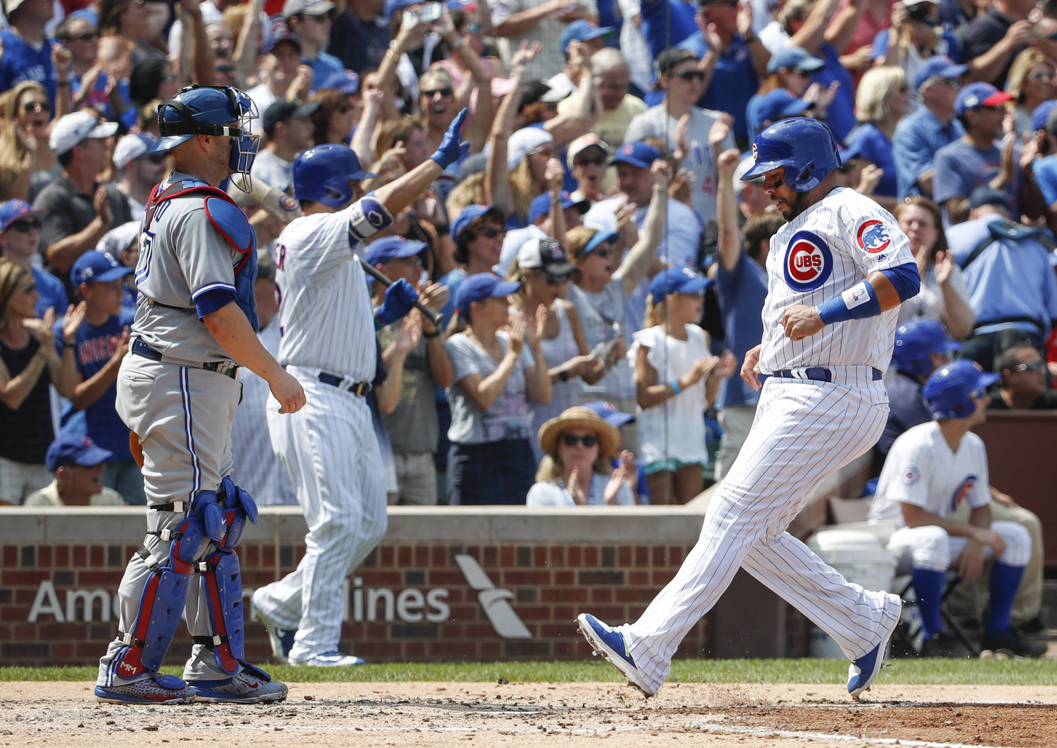 Chicago Cubs' Rene Rivera, right, scores on a three-RBI double hit by Albert Almora Jr. off Toronto Blue Jays' Marco Estrada during the third inning of a baseball game, Sunday, Aug. 20, 2017, in Chicago. (AP Photo/Kamil Krzaczynski)