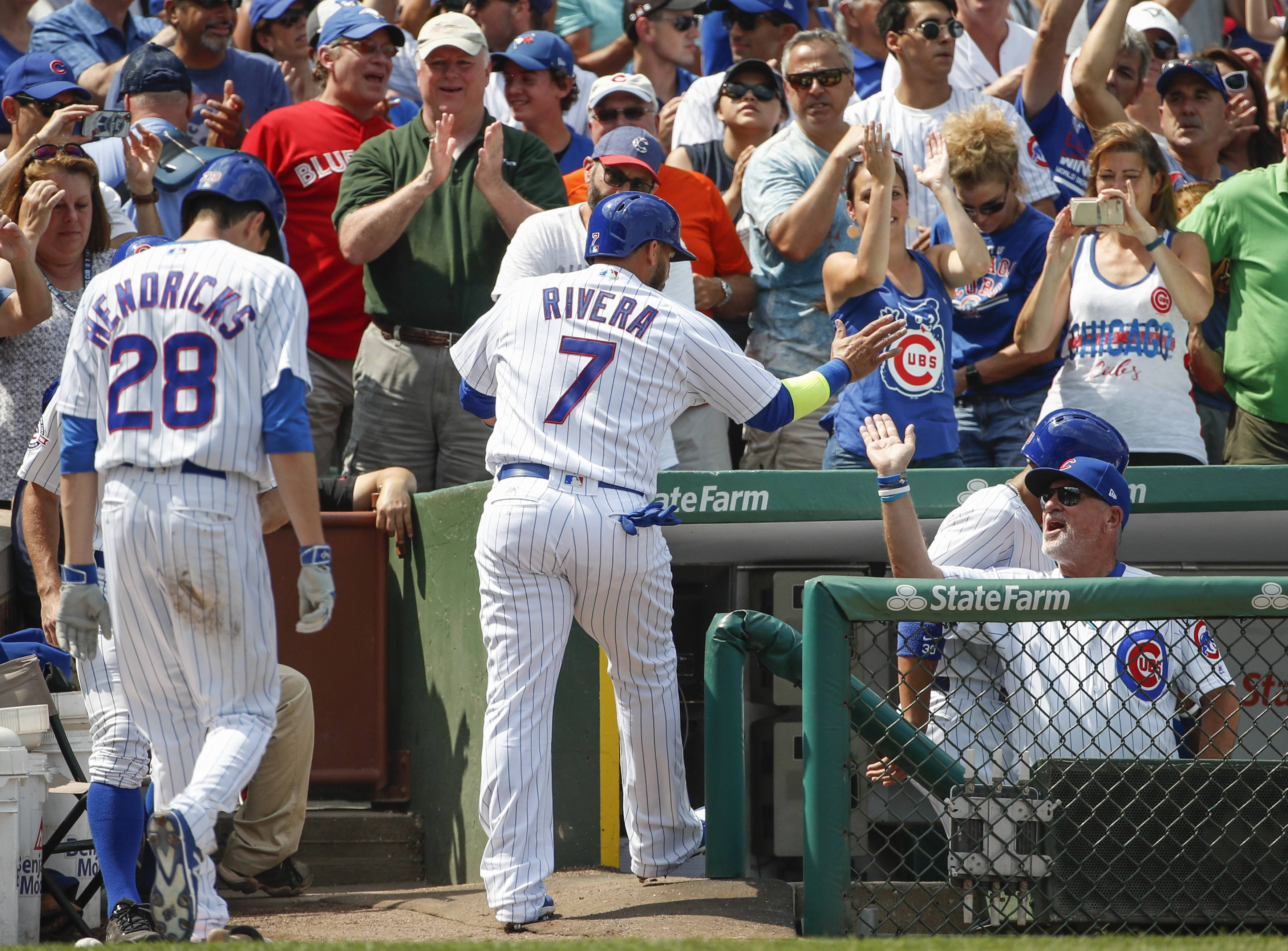 Chicago Cubs' Rene Rivera, center, celebrates after scoring with manager Joe Maddon, right, on a three-RBI double hit by Albert Almora Jr. off Toronto Blue Jays' Marco Estrada during the third inning of a baseball game, Sunday, Aug. 20, 2017, in Chicago.