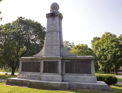 This Wednesday, Aug. 16, 2017 photo shows a statue in Garfield Park that commemorates Confederate soldiers who died in Indiana POW camps. The 35-foot granite tower was moved to Garfield Park in 1928 from its original site marking the mass grave of those who died while held at Camp Morton. While there are no statues, it does have plaques listing the names of 1,616 prisoners. City-County Council President Maggie Lewis said while the monument may be less offensive than others, its location merits a conversation. (Robert Scheer /The Indianapolis Star via AP)