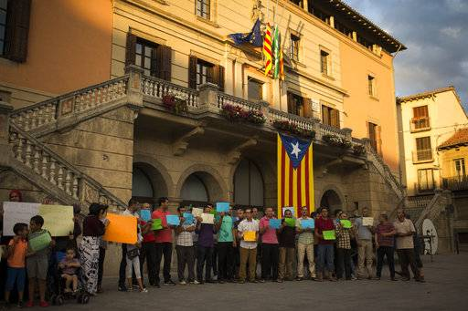 "Members of the local Muslim community gather along with relatives of young men believed responsible for the attacks in Barcelona and Cambrils to denounce terrorism and show their grief in Ripoll, north of Barcelona, Spain, Sunday Aug. 20, 2017. Sheets read in Catalan: ""We all are Barcelona"", ""This affects all of us"", ""Not in the name of Islam"" and ""Everybody against terrorism"". (AP Photo/Francisco Seco)"