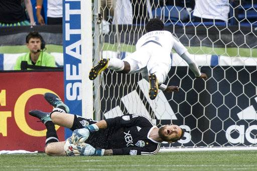 Minnesota United forward Abu Danladi fouls Seattle Sounders goalkeeper Stefan Frei and gets a yellow card during the first half of an MLS soccer match Sunday, Aug. 20, 2017, in Seattle. (Bettina Hansen/The Seattle Times via AP)