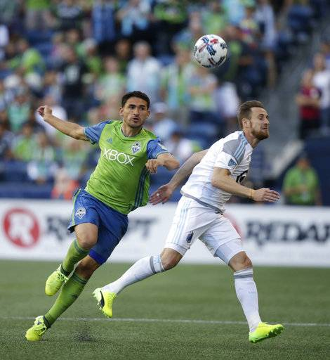 Seattle Sounders' Christian Roldan, left, challenges a Minnesota United player for the ball during an MLS soccer match Sunday, Aug. 20, 2017, in Seattle. (Bettina Hansen/The Seattle Times via AP)