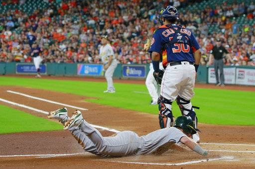 Oakland Athletics' Boog Powell dives safely into home plate as he scores on a throwing error as Houston Astros catcher Juan Centeno stands by in the first inning of a baseball game, Sunday, Aug. 20, 2017, in Houston. (AP Photo/Richard Carson)