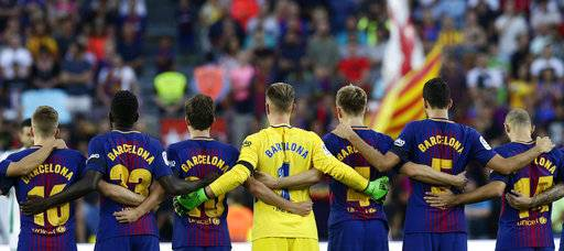 Barcelona players stand for a minute of silence for the victims of the van attacks before a La Liga soccer match between Barcelona and Betis at the Camp Nou stadium in Barcelona, Spain, Sunday, Aug. 20, 2017. Security was stepped up for the match after a terror attack that killed 14 people and wounded over 120 in Barcelona and police put up scores of roadblocks across northeast Spain on Sunday in hopes of capturing a fugitive suspect at large following the vehicle attack. Barcelona players are all wearing shirts with 'Barcelona' on their backs tonight, rather than their names to pay homage to the van attack victims. (AP Photo/Manu Fernandez)