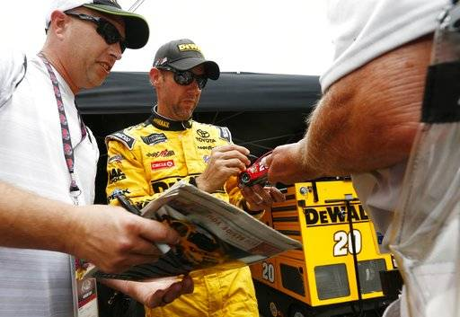 Driver Matt Kenseth signs autographs for fans after practice for the NASCAR Monster Energy Cup Series auto race, Friday, Aug. 18, 2017, in Bristol, Tenn. (AP Photo/Wade Payne)