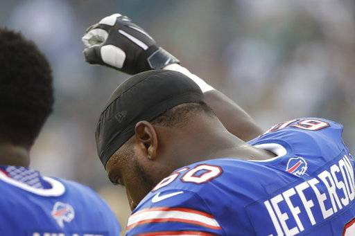 This Aug. 17, 2017 photo shows Buffalo Bills' Cameron Jefferson raising his fist during the national anthem before an NFL preseason football game against the Philadelphia Eagles in Philadelphia. Jefferson says he gained the courage to raise his fist in protest during the anthem once he saw Chris Long hug Eagles teammate Malcolm Jenkins on the opposite sideline on Thursday. (AP Photo/Matt Rourke)