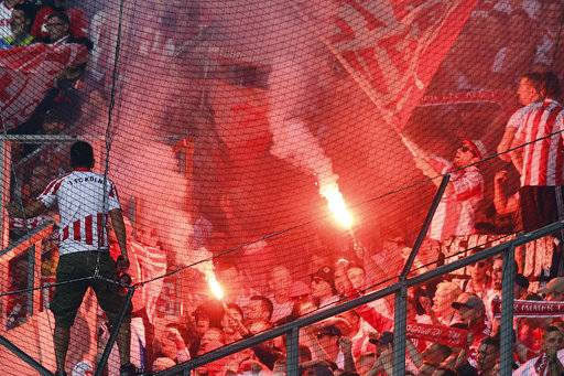 Pyrotechnics ignite as flags are brandished in the Cologne supporters' stands during the German Bundesliga soccer match between Borussia Moenchengladbach and Cologne at the Borussia-Park in Moenchengladbach, Germany, Sunday Aug. 20, 2017. (Federico Gambarini/dpa via AP)