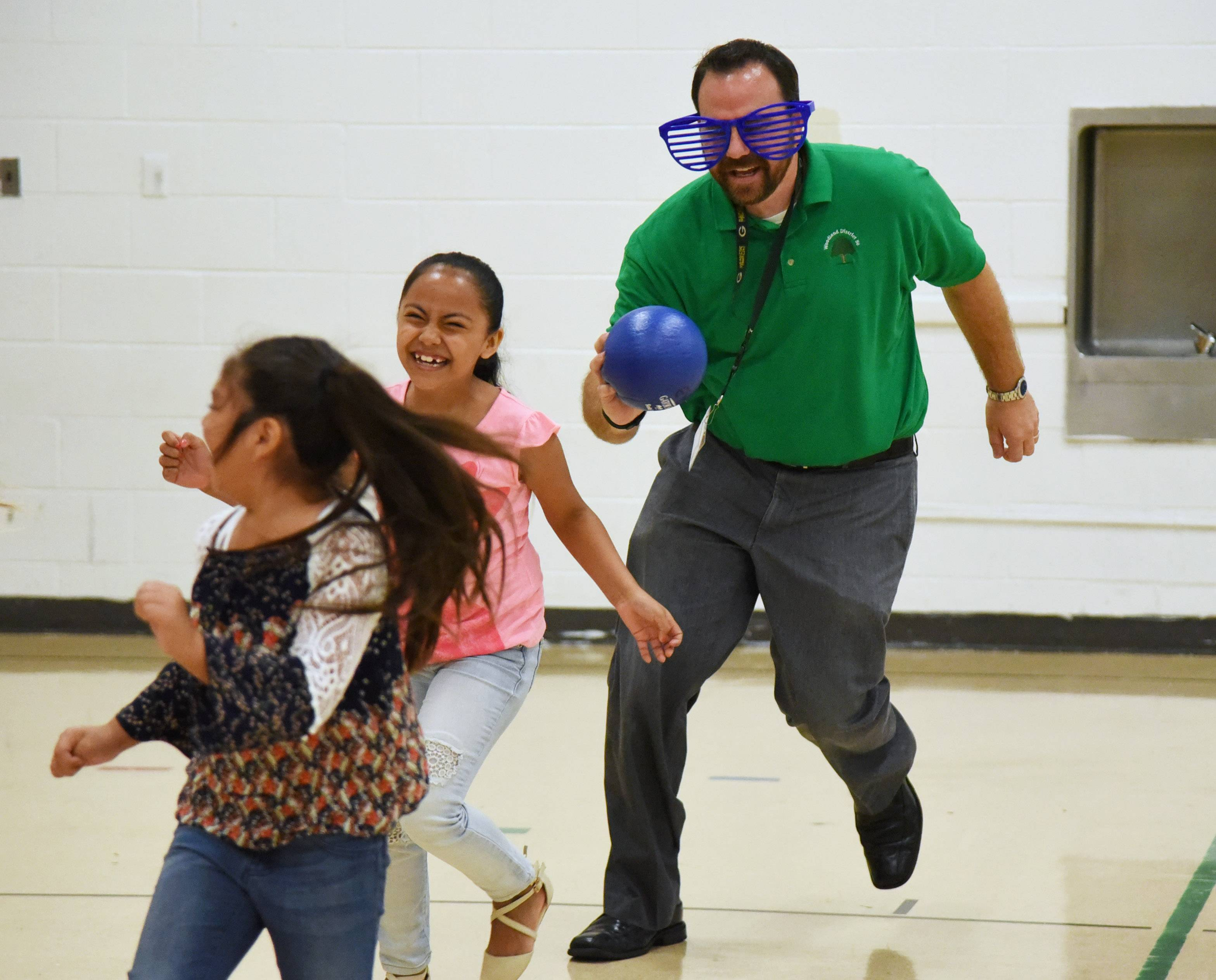 "Ryan Wollberg, the new principal at Woodland Elementary West in Gages Lake, gets to know some of his new students through a game of ""eclipse tag"" Monday, the first day of classes for about 5,800 students in Gurnee-based Woodland School District 50."