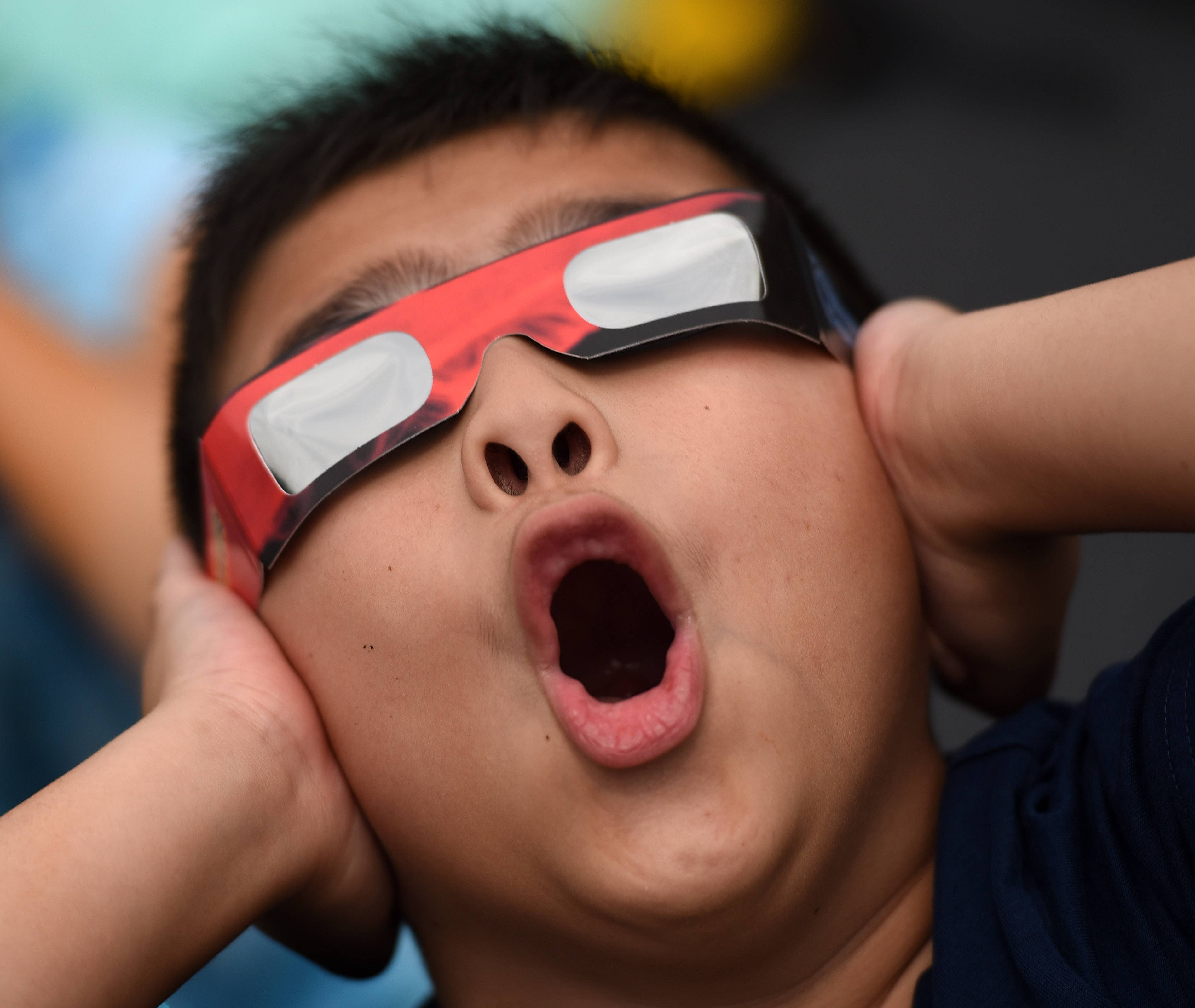 Third-grader Lucas Miller lets out a yell as the moon eclipses the sun at Wayne Elementary School.