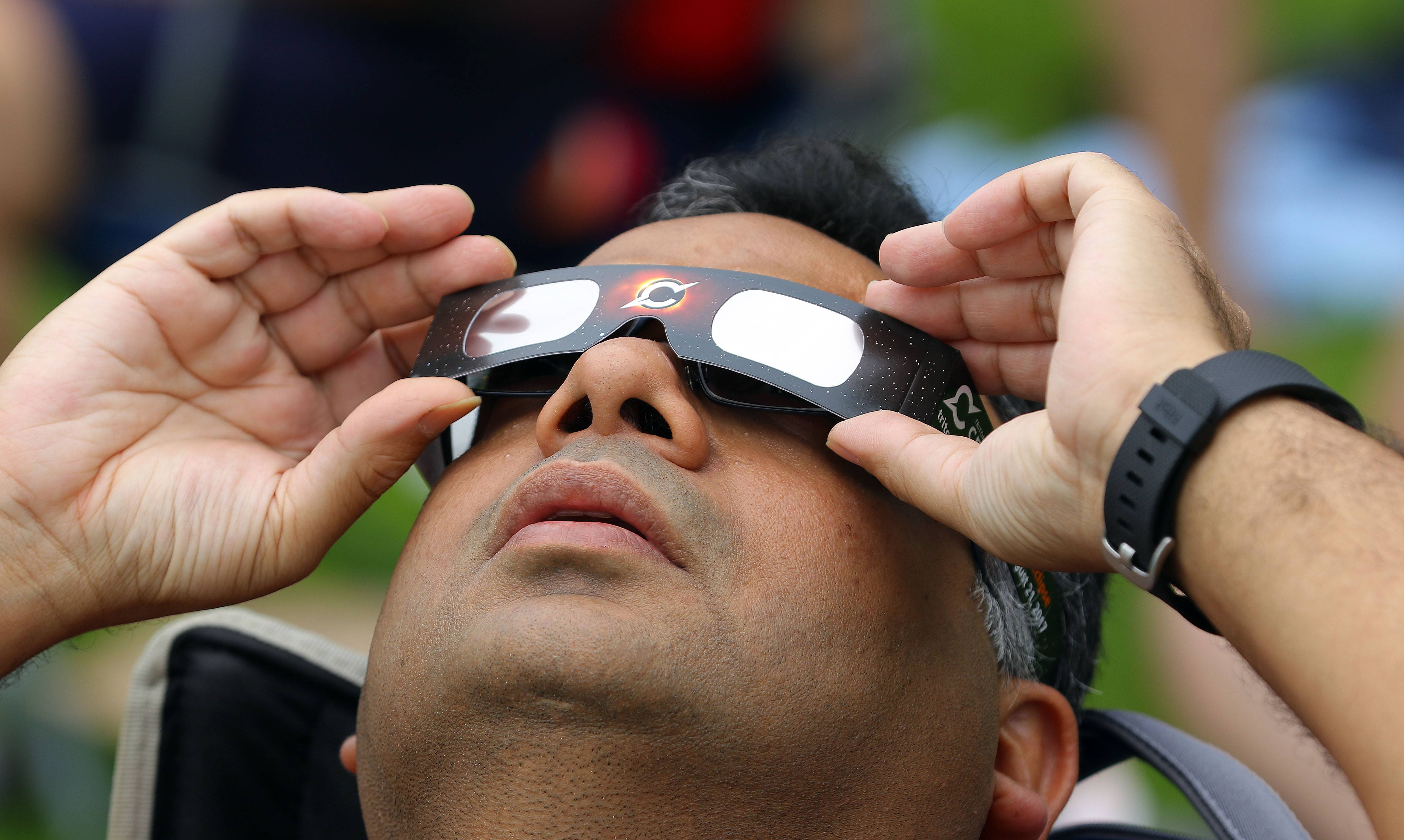 Ashish Purwar of Arlington Heights uses glasses to view the eclipse during Monday's viewing party at Harper College in Palatine.