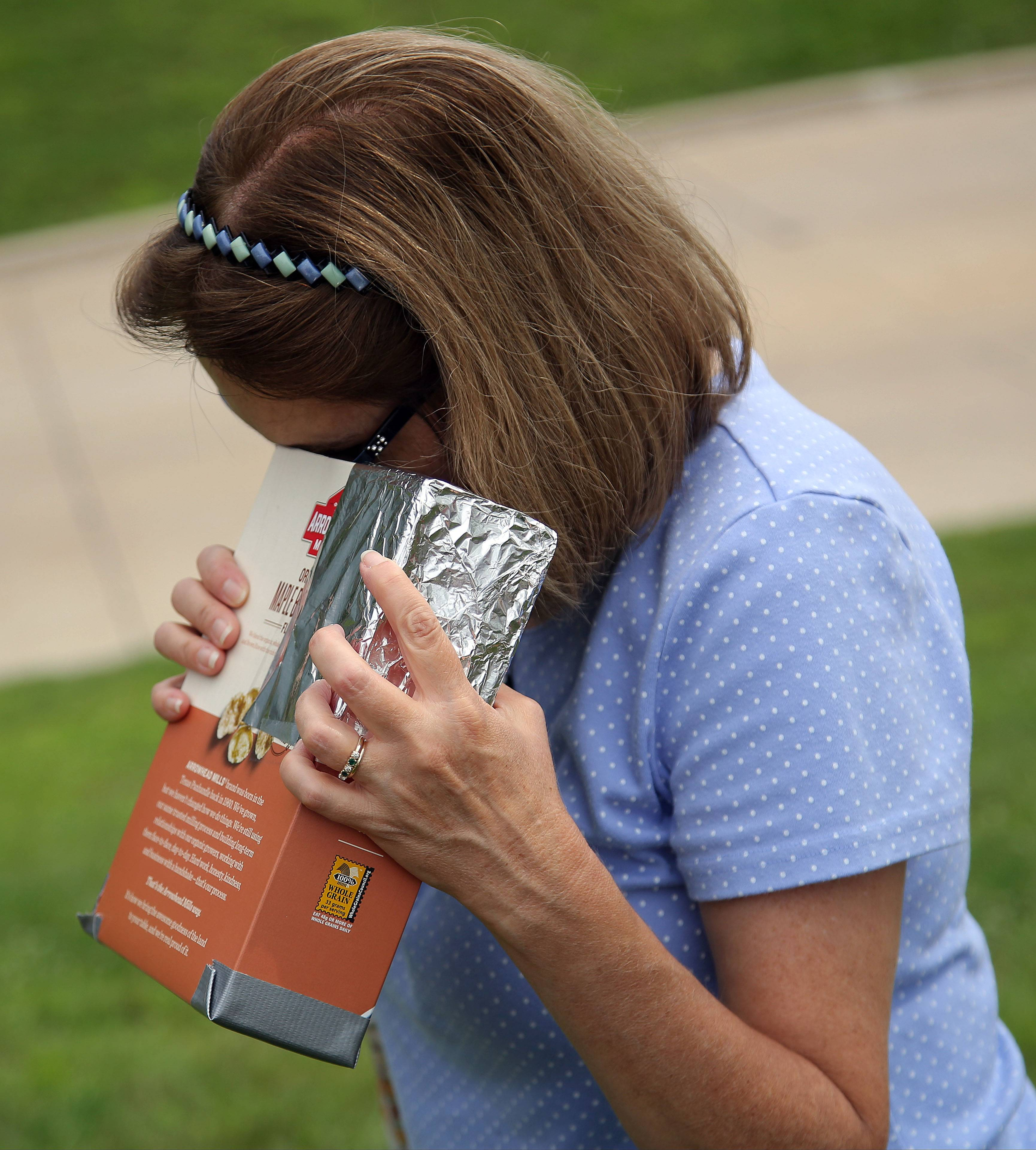 Susan Aubery of Schaumburg uses a pinhole camera in a cereal box to view the eclipse during Monday's solar eclipse viewing party at Harper College in Palatine.