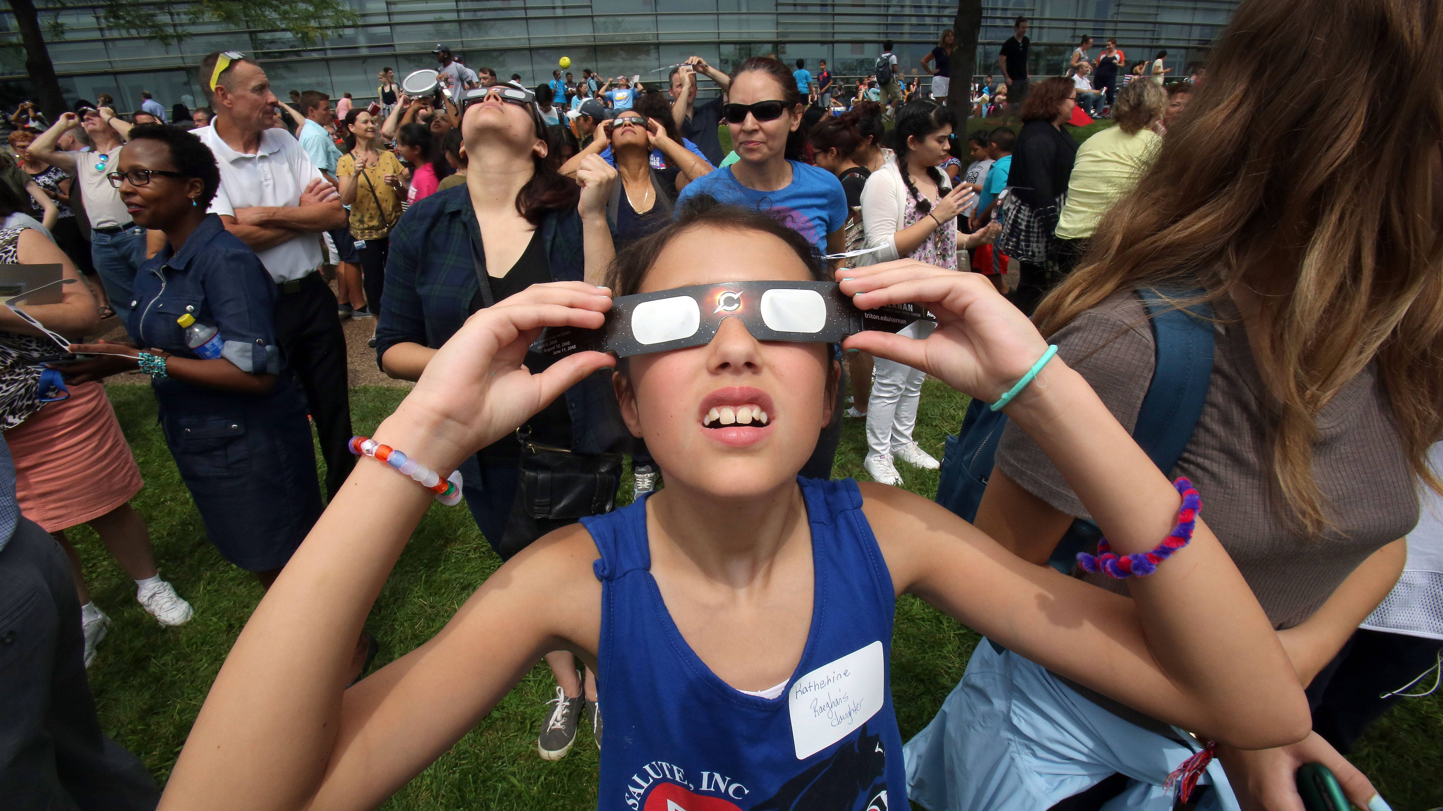 Donning special eclipse glasses, 9-year-old Katherine Graessle takes a look at the sun during Monday's solar eclipse viewing party at Harper College in Palatine.