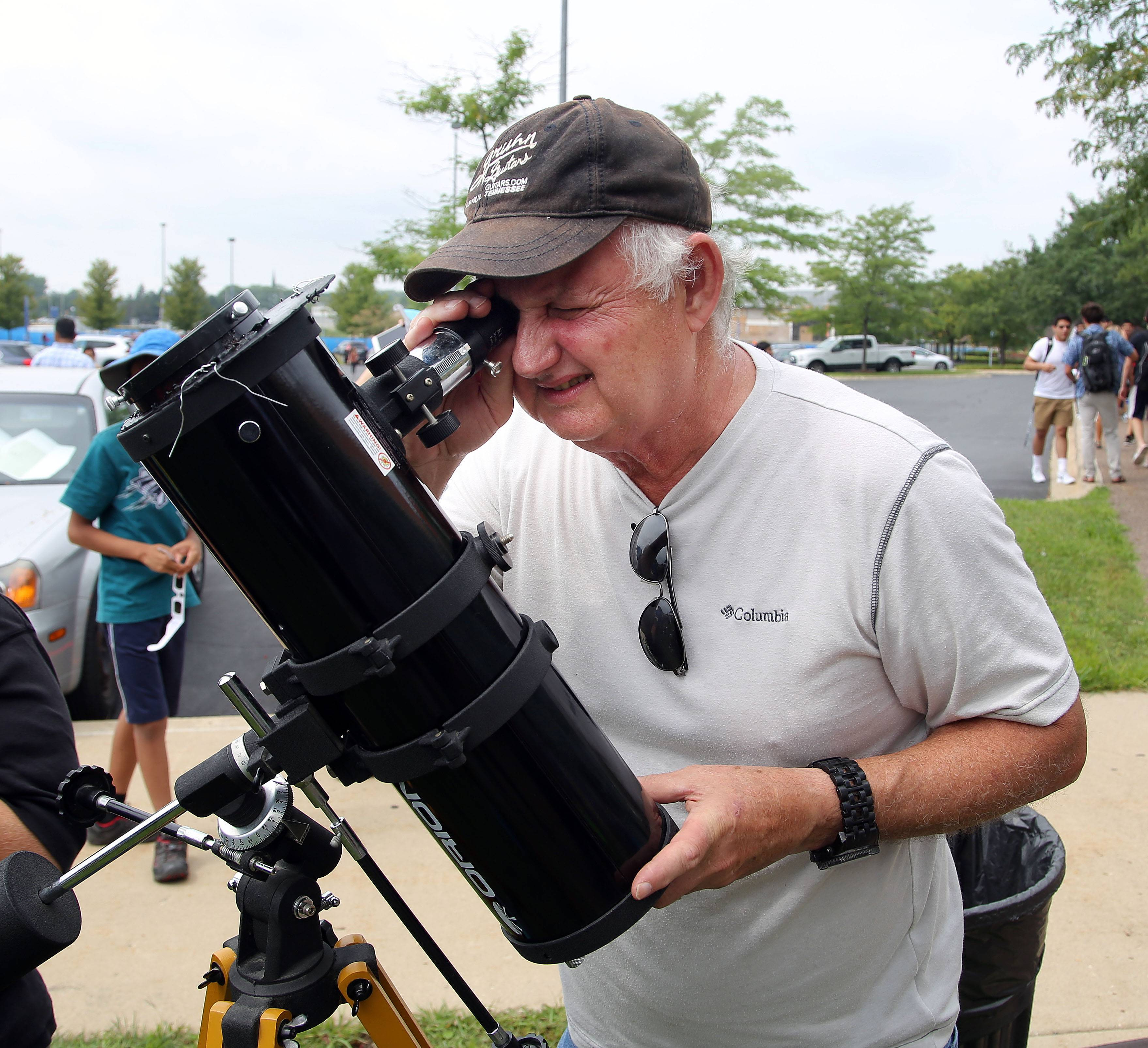 Dennis Dobosiewicz of Wheaton views the eclipse with his telescope during the viewing party at Harper College.