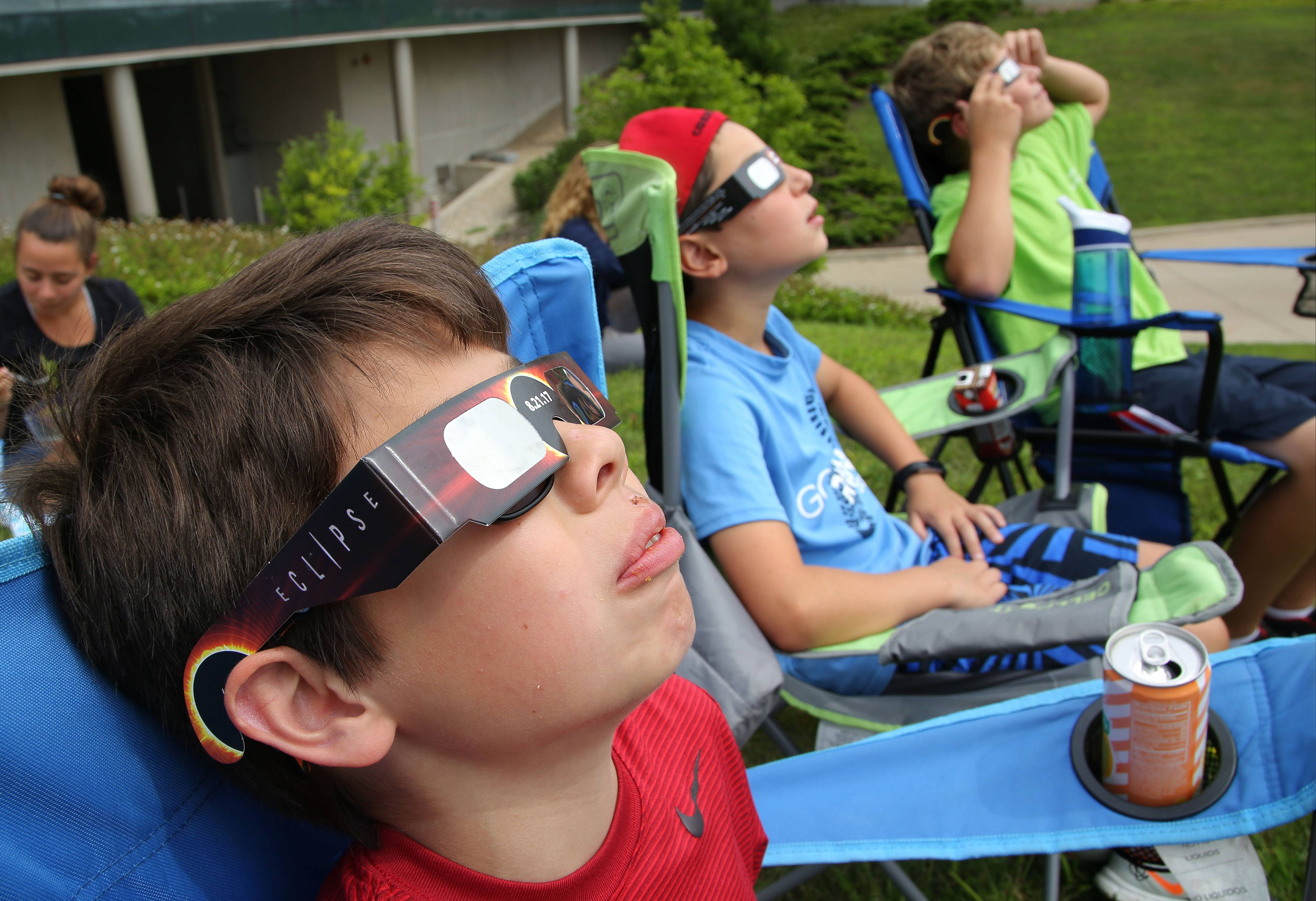 From left, Austin Eckels, Emmet Jordan and Jack Oswald, all 11 and from Palatine, use special glasses during a solar eclipse viewing party Monday at Harper College in Palatine.