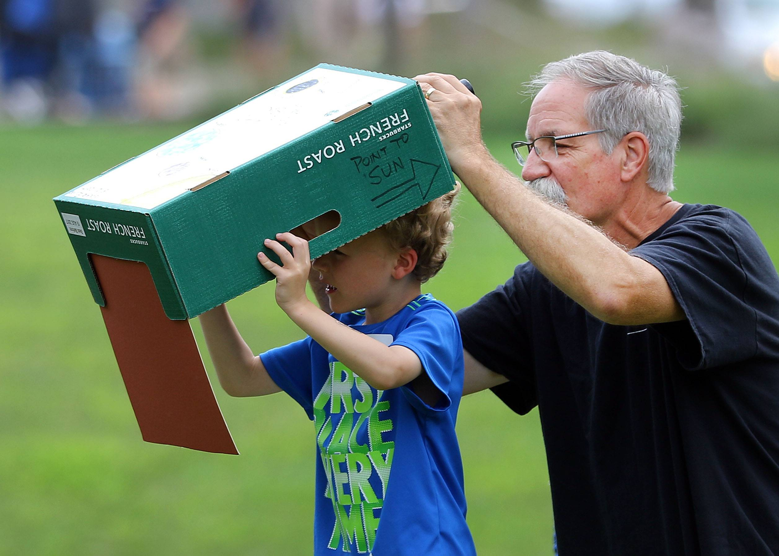 Gary Granzin of Hoffman Estates and his grandson Collin Juracek, 5, of Arlington Heights use a pinhole box to view the eclipse at Harper College.