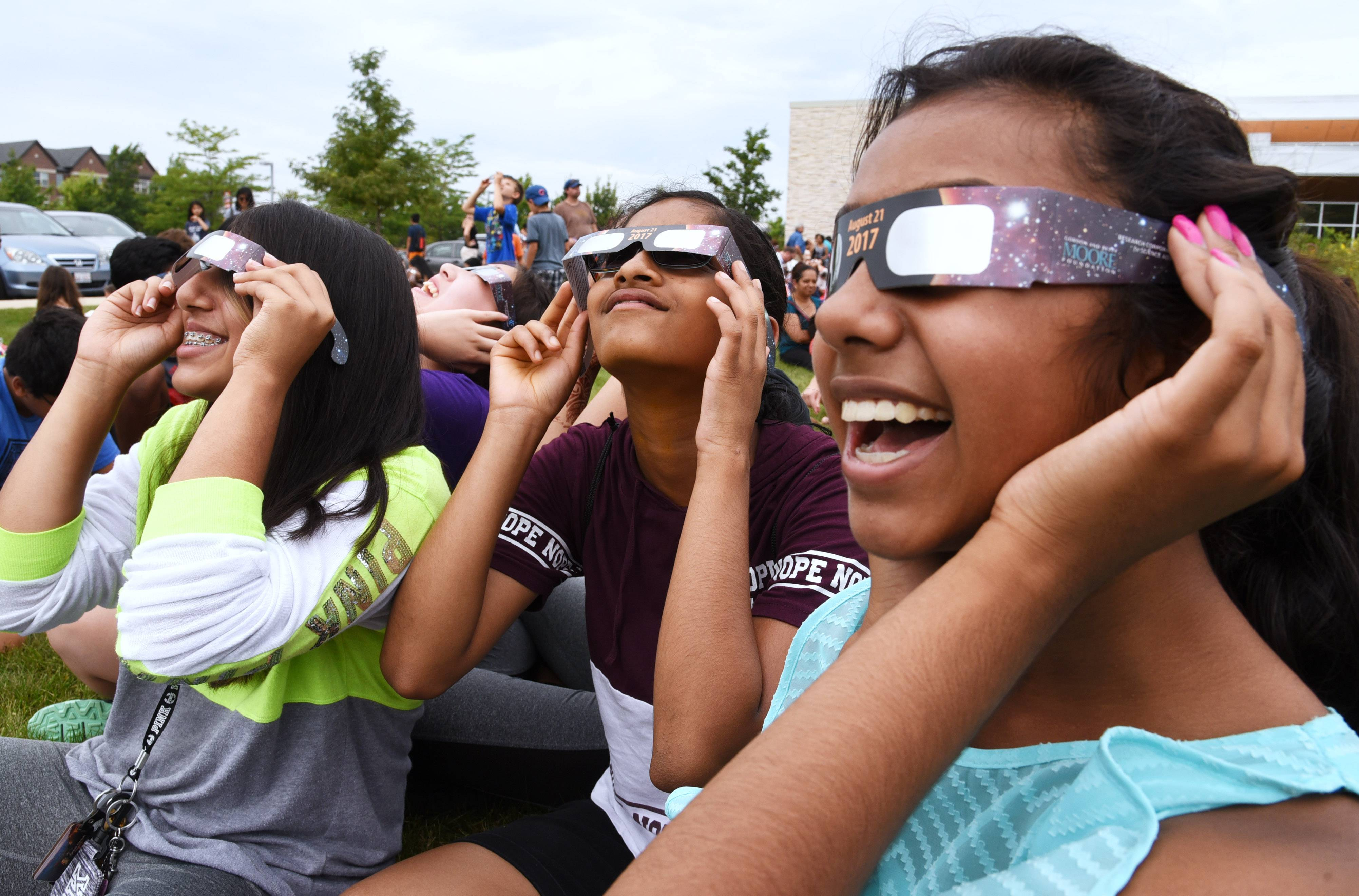From left, Hannah Kapur, Swathi Sureshmoorthy and Ritika Dashaputra watch the eclipse Monday at Aspen Drive Library in Vernon Hills.