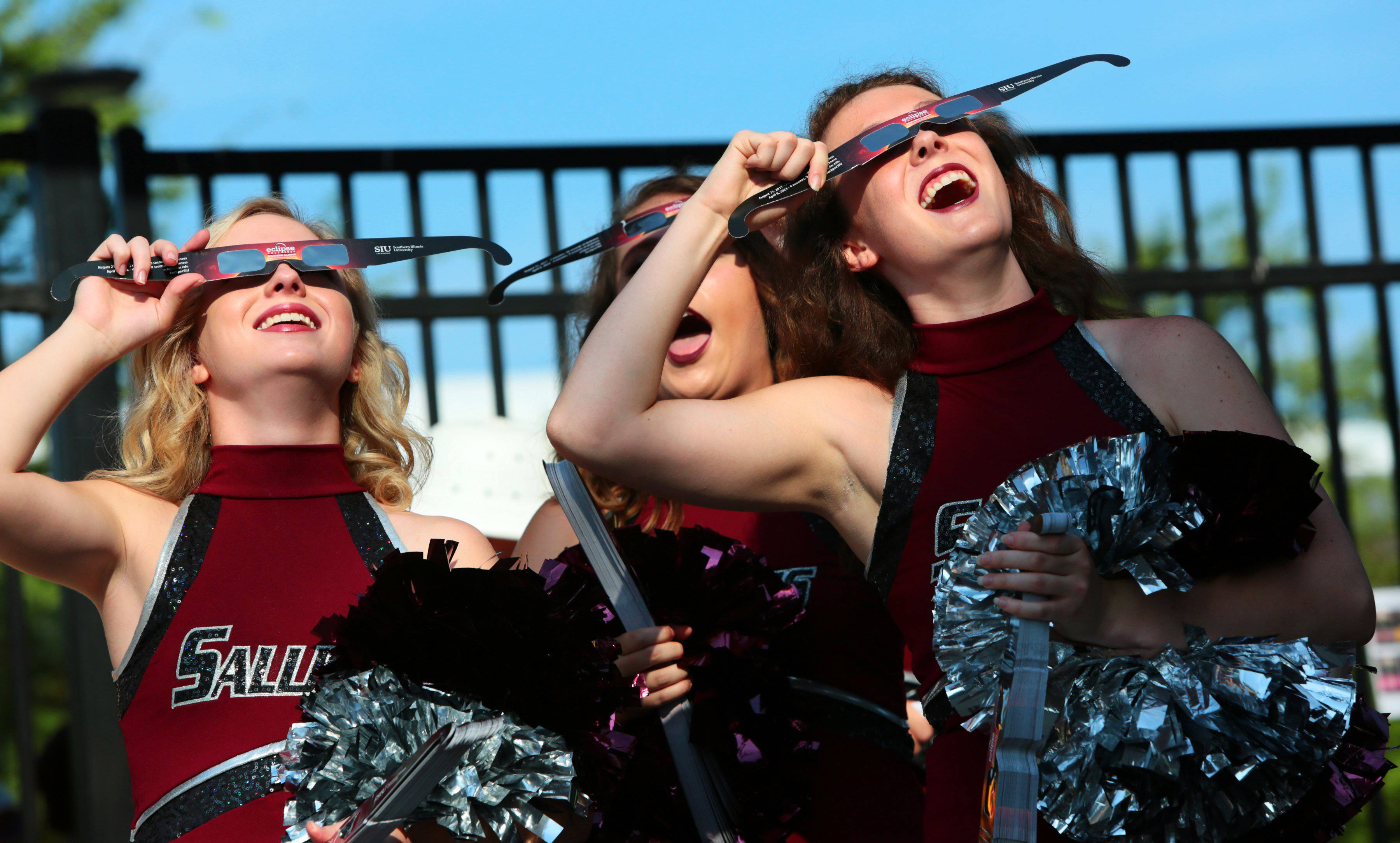 Saluki cheerleaders try out eclipse glasses given to visitors at Saluki Stadium at Southern Illinois University in Carbondale.