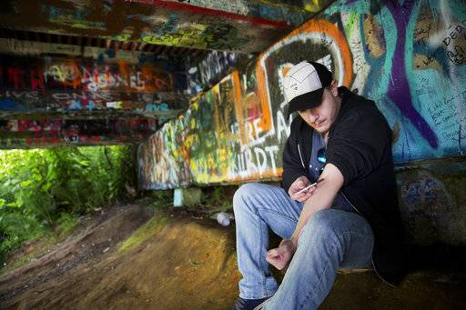 Forrest Wood, 24, injects heroin into his arm under a bridge along the Wishkah River at Kurt Cobain Memorial Park in Aberdeen, Wash., Tuesday, June 13, 2017. Wood grew up here, watching drugs take hold of his relatives, and he swore to himself that he would get out of this place, maybe spend his days in the woods as a park ranger. But he started taking opioid painkillers as a teenager, and before he knew it he was shooting heroin, a familiar first chapter in the story of American addiction. (AP Photo/David Goldman)