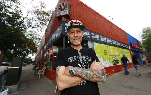 In this Sunday, Aug. 20, 2017, photo, Jim Norris poses for a photo outside of his information cafe called Mutiny in south Denver. Norris is hoping to license his storefront as one of the nation's first legal marijuana clubs. (AP Photo/David Zalubowski)