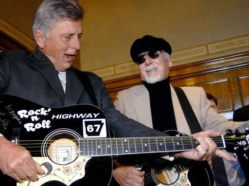 "FILE - In this March 20, 2009 file photo, rockabilly musician Albert ""Sonny"" Burgess, right, and Arkansas Gov. Mike Beebe jam on guitars before a bill-signing at the Capitol in Little Rock, Ark. Burgess, who was an early pioneer of what became known as rockabilly music, died Friday, Aug. 18, 2017, in Little Rock. He was 88. (AP Photo/Mike Wintroath, File)"