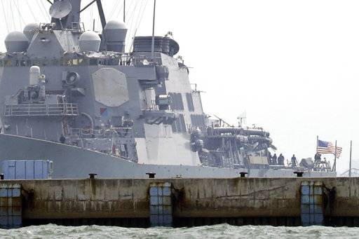 "An American flag is flown off the stern of The USS John S. McCain docked at Changi naval base after its accident Monday, Aug. 21, 2017 in Singapore. The USS John S. McCain was docked at Singapore's naval base with ""significant damage"" to its hull (blocked by berth) after an early morning collision with the oil tanker Alnic MC as vessels from several nations searched Monday for missing U.S. sailors. (AP Photo/Wong Maye-E)"