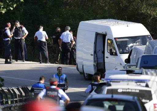 Police bomb squad officers work by a road near Subirats, Spain, Monday, Aug. 21, 2017. A police operation was underway Monday in an area west of Barcelona, and a Spanish newspaper reports that the fugitive in the city's van attack has been captured. Regional police said officers shot a man wearing a possible explosives belt in Subirats, a small town 45 kilometers (28 miles) west of Barcelona. (AP Photo/Emilio Morenatti)