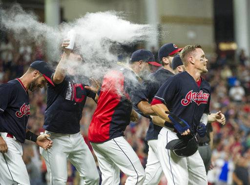 Cleveland Indians' Brandon Guyer, right, is mobbed by his teammates after scoring the winning run in the bottom of the ninth inning of a baseball game against the Boston Red Sox in Cleveland, Monday Aug. 21, 2017. (AP Photo/Phil Long)