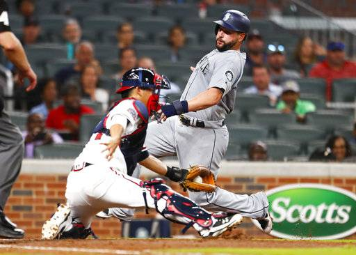 Seattle Mariners Yonder Alonso (10) avoids the tag of Atlanta Braves catcher Kurt Suzuki (24) at home to score in the fourth inning of a baseball game, Monday, Aug. 21, 2017, in Atlanta. (AP Photo/Todd Kirkland)