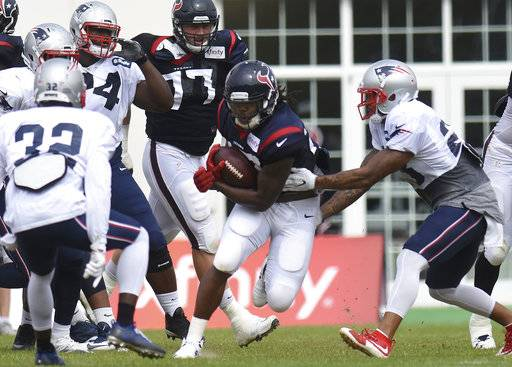 Houston Texans running back D'Onta Foreman tries to get past New England Patriots' Devin McCourty (32) and Patrick Chung (23), right, during a joint practice with the two NFL football teams in White Sulphur Springs, W.Va., Wednesday, Aug. 16, 2017. (AP Photo/Chris Jackson)