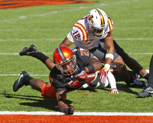 FILE - In this Saturday, Oct. 8, 2016 file photo, Oklahoma State running back Justice Hill (27) dives into the end zone with a touchdown in front of Iowa State defensive back Jarnor Jones (12) in an NCAA college football game in Stillwater, Okla. Hill isn't as well known as star offensive teammates Mason Rudolph and James Washington. He might be after this season. (AP Photo/Sue Ogrocki, File)
