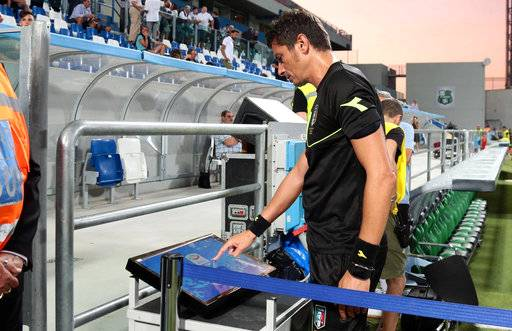 In this photo taken on Sunday, Aug. 20, 2017, referee Antonio Damato checks the VAR (video assistant referee) monitor prior to the Serie A soccer match between Genoa and Sassuolo at the Mapei Stadium in Reggio Emilia, Italy. The introduction of video review in Serie A was meant to eliminate controversial decisions. However, debate continues to rumble on after the first weekend using the new technology. (Elisabetta Baracchi/ANSA via AP)