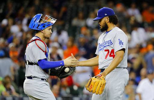 Los Angeles Dodgers relief pitcher Kenley Jansen (74) and catcher Yasmani Grandal celebrate after the final out against the Detroit Tigers in the ninth inning of a baseball game in Detroit, Friday, Aug. 18, 2017.(AP Photo/Paul Sancya)