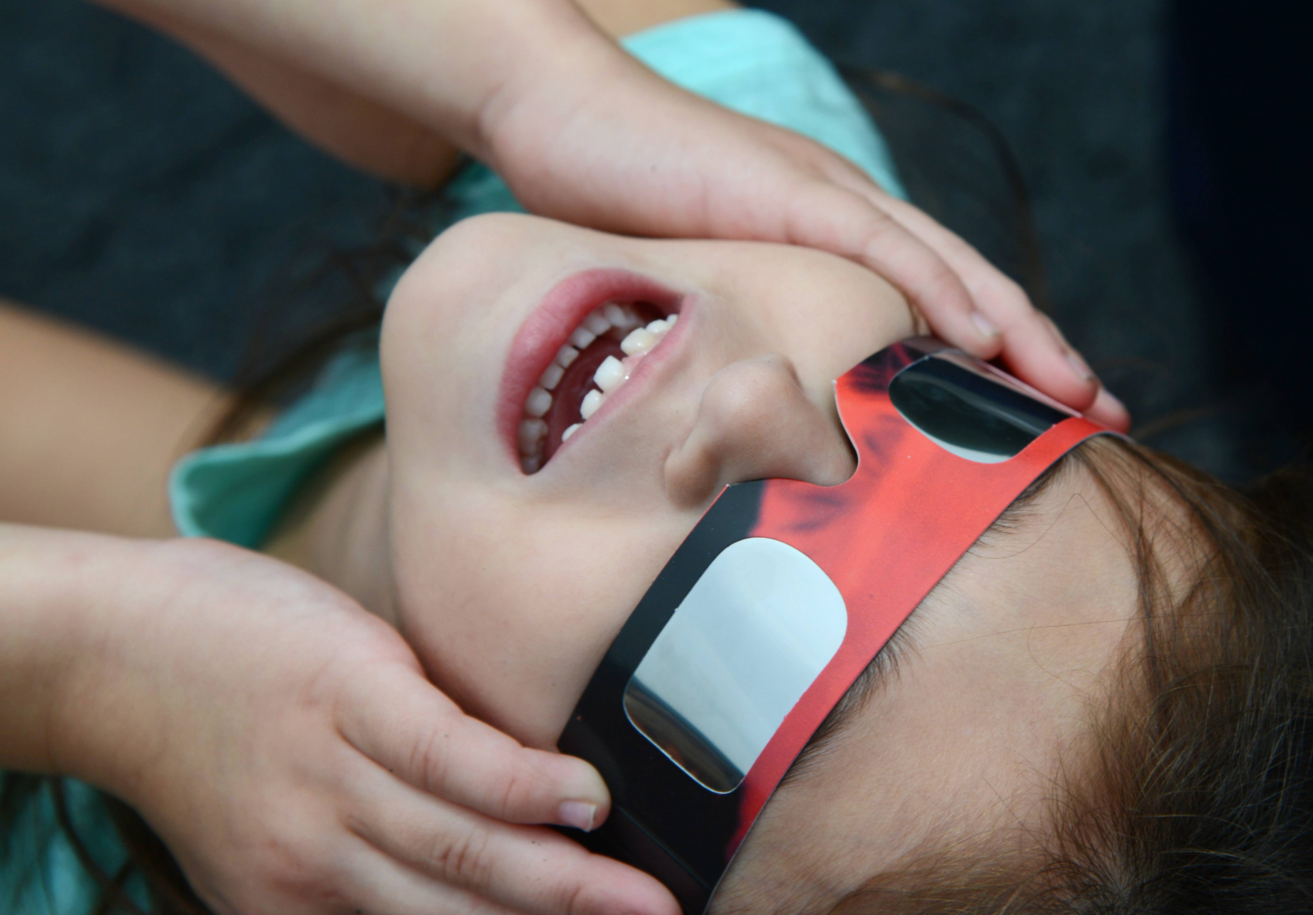 Kindergartner Sophia San Fillippo cranes her neck to watch the solar eclipse from Wayne Elementary School on Monday.