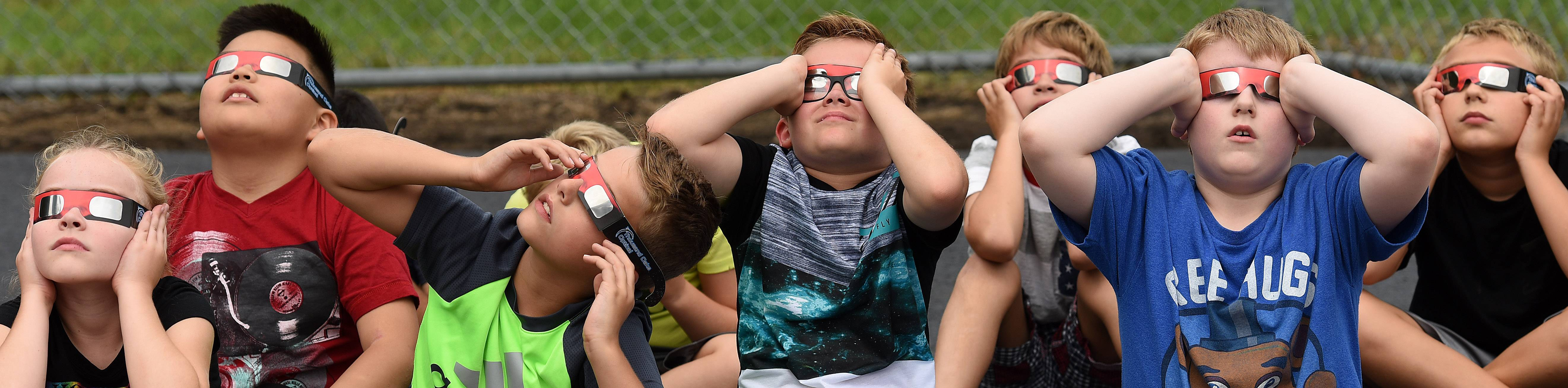 Third-graders at Wayne Elementary School hold their glasses tight as they watch the solar eclipse on Monday.