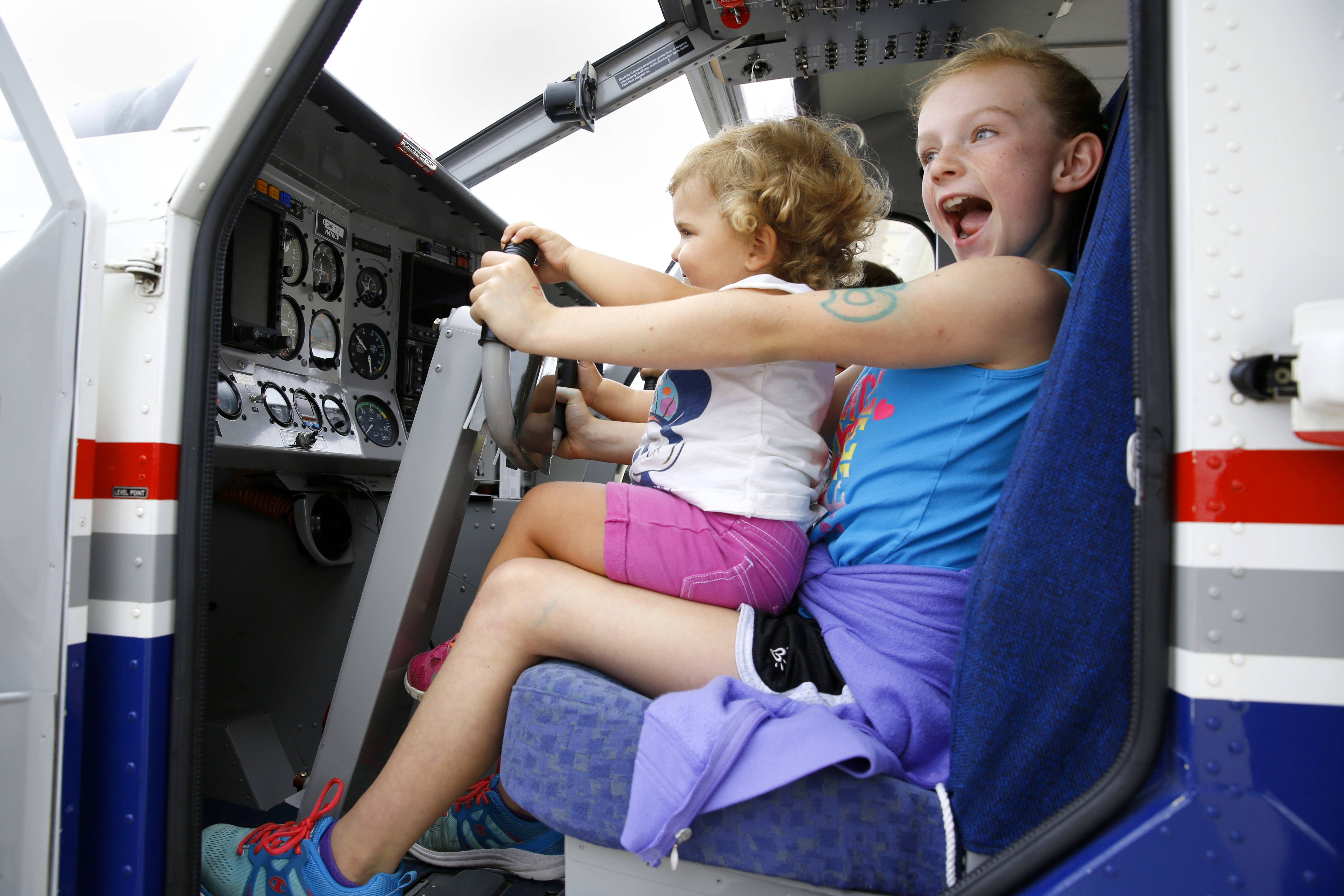 Gracie Perry, 9, of West Chicago, holds 1-year-old Jordyn Pater of St. Charles, as they enjoy their time behind the stick of an airplane during Tuesday's Back to School Celebration sponsored by the DuPage Airport Authority and the city of West Chicago.