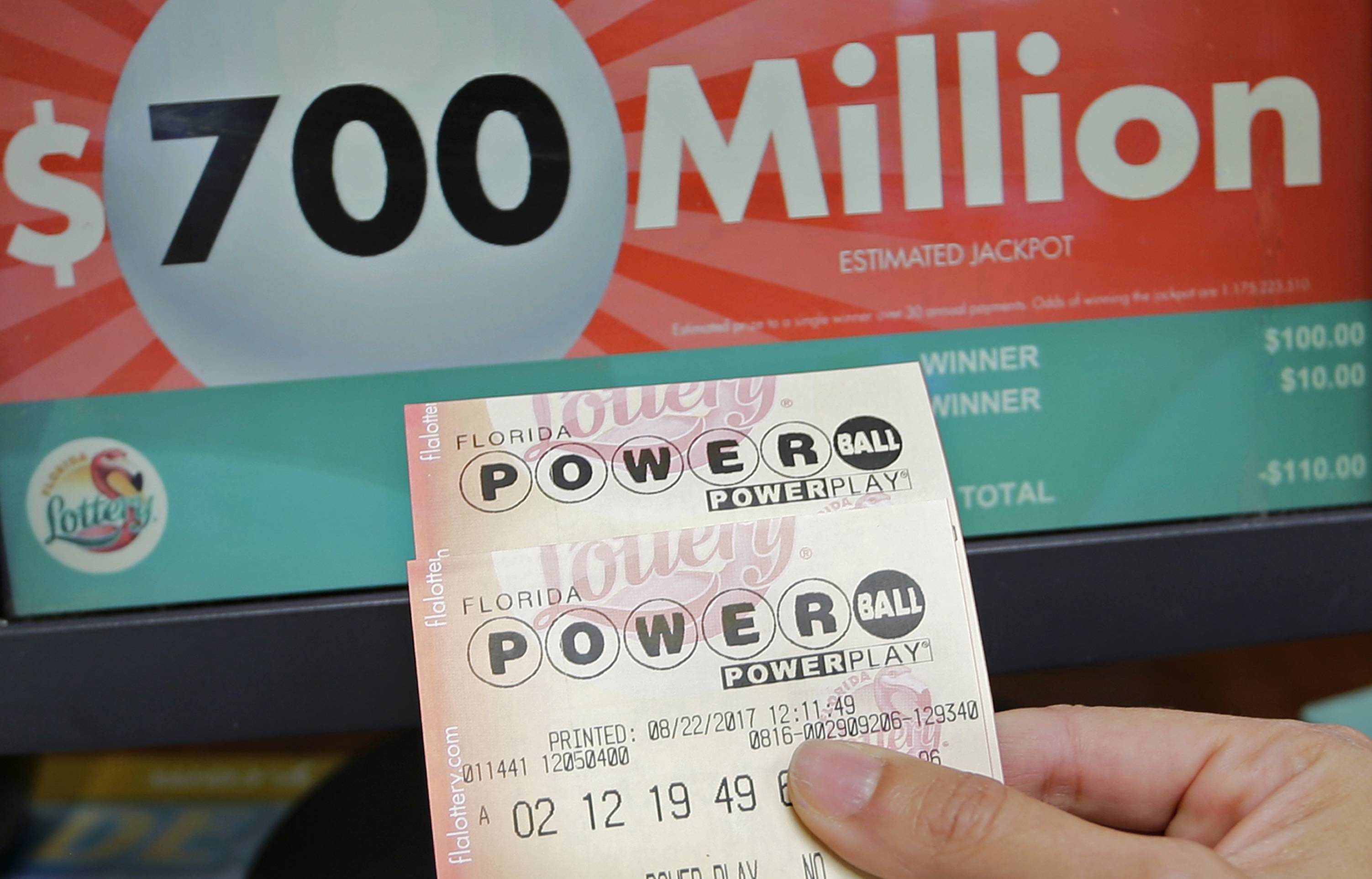 A customer shows her purchased Powerball tickets for Wednesday's drawing, Tuesday, Aug. 22, 2017, in Hialeah, Fla. The winner could take the $700 million annuity option (paid out over 29 years) or the $443.3 million cash prize, minus state and federal taxes.