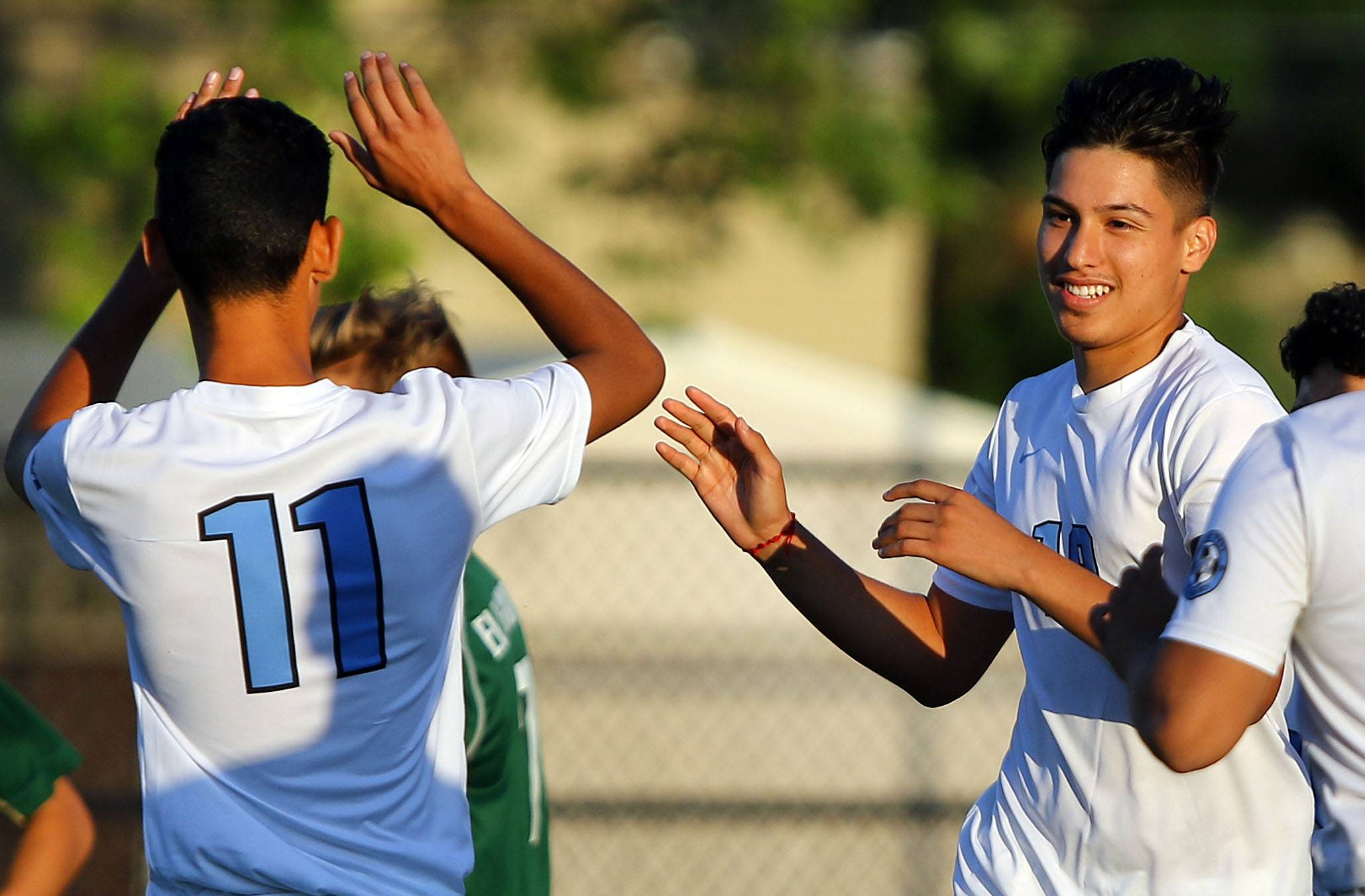 Maine West's Jason Ybrra (11) high-fives Osmar Vega after his goal against Elk Grove on Tuesday in Des Plaines.