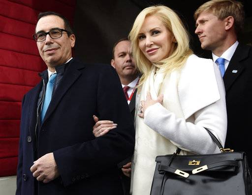"FILE - In this Friday, Jan. 20, 2017, file photo, then Treasury Secretary-designate Stephen Mnuchin and his then-fiancee, Louise Linton, arrive on Capitol Hill in Washington, for the presidential inauguration of Donald Trump. Linton responded to a social media critic on Aug. 21, 2017, telling the mother of three that that she was ""adorably out of touch.� Mnuchin and Linton were married in June. (Saul Loeb/Pool Photo via AP, File)"