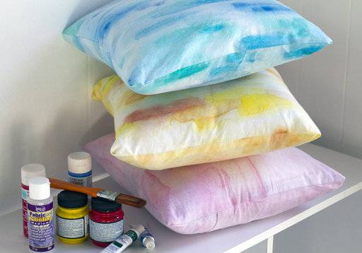 This Aug. 20, 2017, photo in Hopkinton, N.H, shows three pillows created using different techniques and some of the necessary supplies, including fabric painting medium, craft paint and liquid watercolor paint. Creating a watercolor effect on fabric is easy, and depending on the method used, inexpensive. (AP Photo/Holly Ramer)