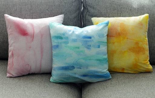 This Aug. 20, 2017, photo in Hopkinton, N.H., shows three pillows created using different techniques for achieving a watercolor effect on fabric. Getting artwork off the walls and onto a sofa is as easy as painting fabric and using it to cover throw pillows.