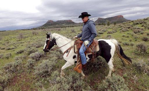 FILE - In this May 9, 2017, file photo, Interior Secretary Ryan Zinke rides a horse in the new Bears Ears National Monument near Blanding, Utah. Conservation groups are airing TV ads, planning rallies and creating parody websites in a last-minute blitz to persuade Interior Secretary Ryan Zinke to refrain from reducing or eliminating large swaths of land across the country that have been designated as national monuments, Tuesday, Aug. 22, 2017. (Scott G Winterton/The Deseret News via AP, File)