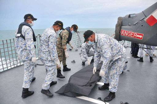 In this photo released by the Royal Malaysian Navy, navy sailors cover an unidentified body on to the deck of KD Lekiu frigate after it was recovered in the waters off the Johor coast of Malaysia, Tuesday, Aug. 22, 2017. The commander of the U.S. Pacific Fleet said some remains of Navy sailors were found in a compartment of the USS John McCain on Tuesday, a day after the warship's collision with an oil tanker in Southeast Asian waters left 10 sailors missing. (Royal Malaysian Navy via AP)