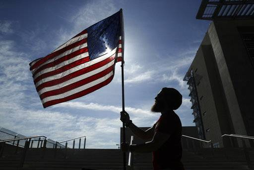 FILE - In this April 10, 2017 file photo, a protester holds up a flag outside of a federal courthouse in Las Vegas in support of defendants accused of wielding weapons against federal agents during a 2014 standoff involving cattleman and states' rights advocate Cliven Bundy. A federal jury in Las Vegas is deliberating again Monday, Aug. 21, 2017, in the retrial of four men accused of wielding assault weapons against federal agents in a 2014 standoff near the Nevada ranch of anti-government figure Cliven Bundy. Jurors returned to work Monday, after spending a little more than two days last week going over five weeks of evidence in the case against four defendants. (AP Photo/John Locher, File)