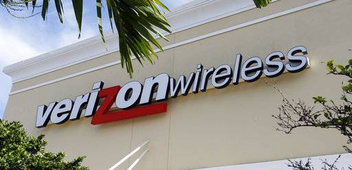 This Friday, Aug. 11, 2017, photo shows a Verizon wireless sign in Miami. Verizon is raising the price on its unlimited plan while introducing a slightly cheaper, more limited version of it as wireless carriers battle each other for customers. (AP Photo/Alan Diaz)