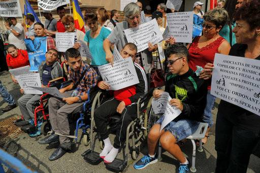 "Disabled people take part in a protest outside the Labour Ministry in Bucharest, Romania, Tuesday, Aug. 22, 2017. Hundreds of disabled people joined the protest to express their anger at a government emergency decree that changes the current law and no longer obliges companies with more than 50 employees to hire a number of disabled people or use the services of a department that hires special needs personnel which could lead to 2,000 disabled people losing their jobs. Papers read ""We don't want assistance , we want to be active and involved"" and ""You killed our hope with your decree"". (AP Photo/Vadim Ghirda)"